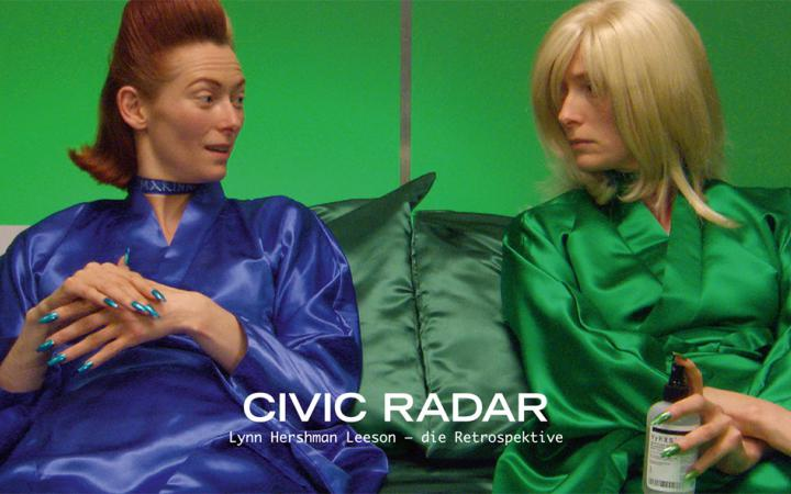 A woman in two different appearance. On the left side in the blue silk coat and brown hair, on the right side in the green silk coat and blond hair. Both sit together and look at each other.