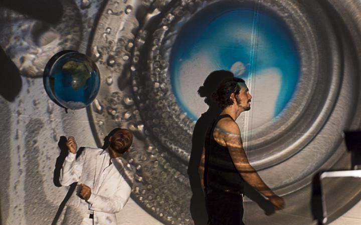 Ein schwarz gekleideter Mann steht im Profil vor einem großen silbernen Kreiselement, dessen Mitte bläulich ist. Hinter ihm hält ein weiß gekleideter Mann einen Luftballon in seinen Händen.