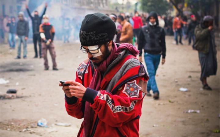 Ein Mann in roter Jacke und schwarzer Mütze. Sein linkes Auge ist verbunden. Er trägt eine Brille und schaut auf etwas, was er in seinen Händen hält. Im Hintergrund eine Vielzahl von Menschen.