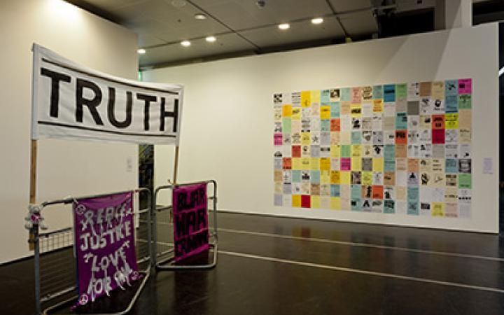 Auf der linken Bildhälfte sind drei Transparente zu sehen. Auf einem steht 'Truth'. Auf der rechten Bildhälfte kleben an einer Wand viele Papiere. Sie sind farbig und mit Texten versehen. Sie bilden in ihrer Masse eine großes Rechteck.