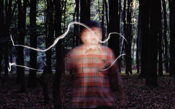 Ein verschwommener Mann, der im Wald steht