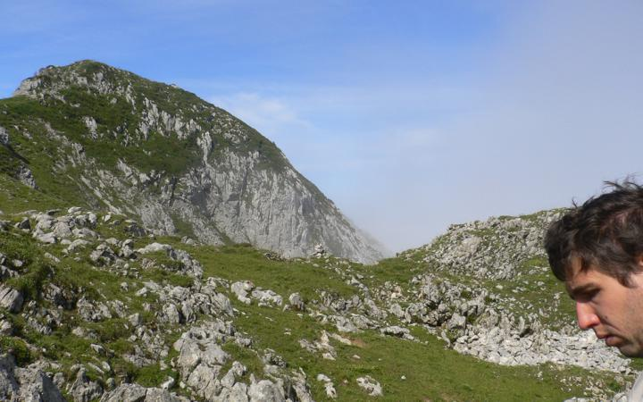 Im Hintergrund Berge, im rechten Bildrand ein Gesicht eines jungen Mannes