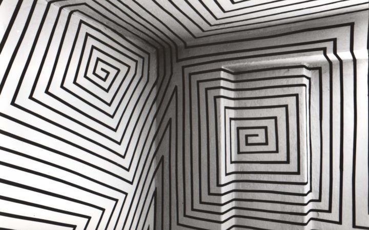 Schwarze orthogonale Ornamente verteilen sich über einen ganzen Raum, der weiß gestrichen ist.