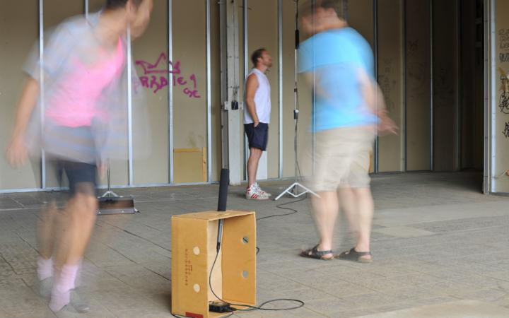 A banana box into which a microphone was installed. To the crate running around two men. By distorted blur they are not visible. In the background: Another person in front of a microphone.