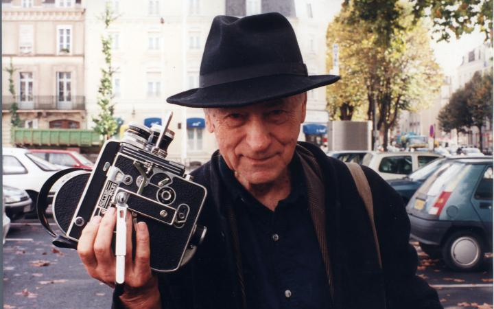 Jonas Mekas with a hat on his head and a camera in hand