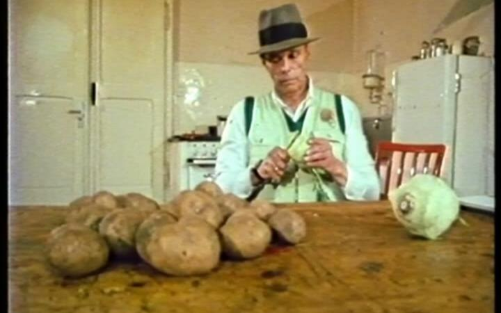 A man sitting at a table and peels potatoes and turnips