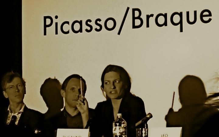 From left to right: Two men and a woman at a table. She talks, keeping a pencil in her right hand. On the table name tags. In the background is 'Picasso / Braque' to read.