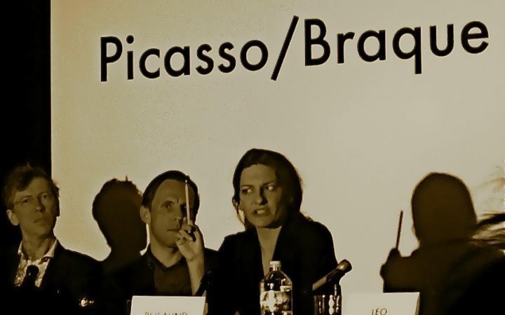 Von links nach rechts: Zwei Männer und eine Frau an einem Tisch. Sie redet und hält dabei einen Bleistift in ihrer rechten Hand. Auf dem Tisch stehen Namensschilder. Im Hintergrund ist 'Picasso/Braque' zu lesen.