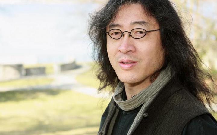 Ein Mann mit Brille und langen Haaren steht vor einem Baum