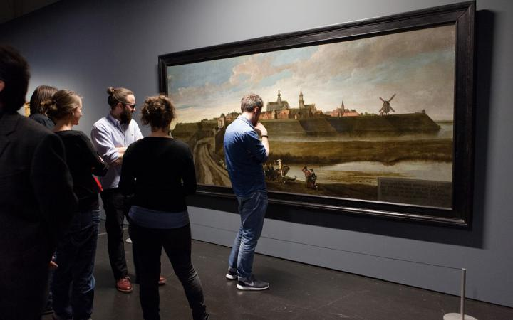 Persons in the exhibition »Mapping Spaces« in front of a painting
