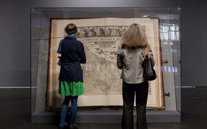 Der Klencke Atlas (1660) ist einer der größten Atlanten der Welt. Aufgeschlagen steht er in einer ihn schützenden Glaskonstruktion. Zwei Frauen in Rückenansicht betrachten ihn.