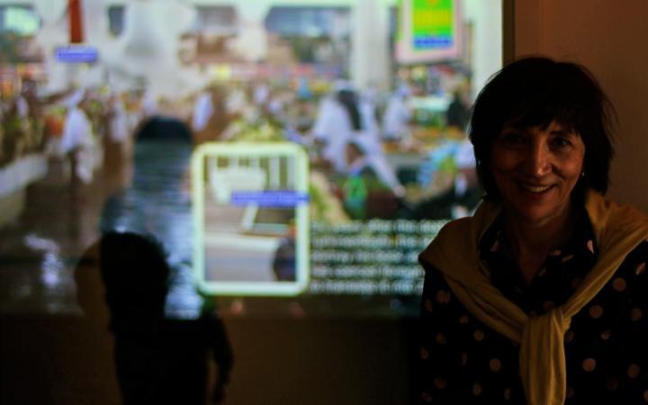 Eine Frau im rechten Rand des Bildes. Im Hintergrund eine Leinwand, die einen Desktop mit offenen Programmen zeigt