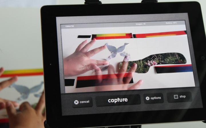 Per iPad werden zwei Kinderhände aufgezeichnet, die an einer Papiercollage arbeiten.