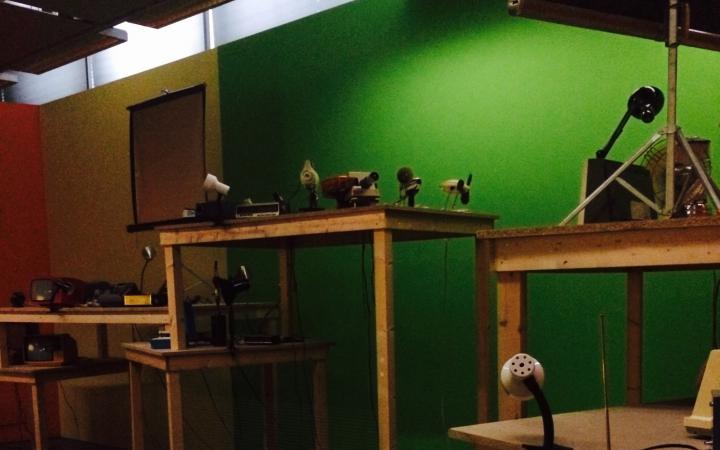 Sechsteilige Tischinstallation vor orange-gelb-grüner Wand. Lampen, Ventilatoren und weitere Haushaltsutensilien sind auf den Tischen zu erkennen.