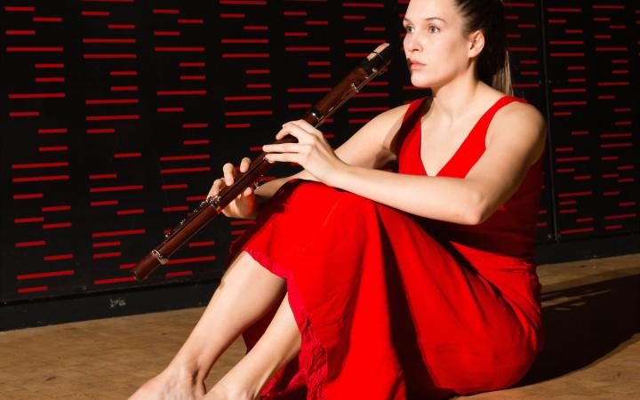 A woman dressed in red sitting on the floor. In her hands she holds a flute.