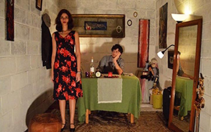 Blick in Zimmer mit Spiegel und Tisch. Dieser hat eine grüne Tischdecke. An dem Tisch sitzt ein Mann. Daneben steht eine Frau in einem schwarz rot geblümten Kleid.