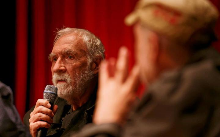Ein Mann mit weißem Bart am Mikrophon: Louis Bec