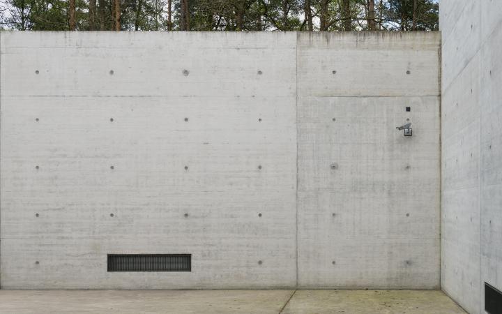 Eine Betonmauer mit einer Lüftung links und einer Überwachungskamera rechts oben
