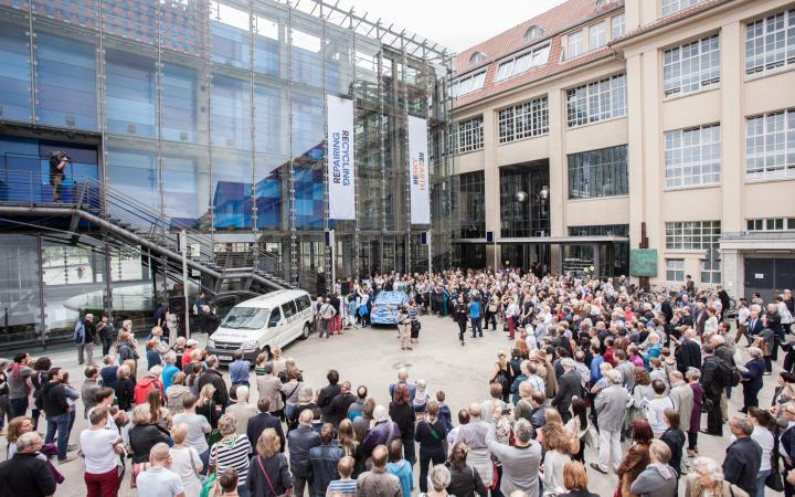 Eine Menschenmenge vor dem ZKM-Eingang versammelt sich um ein blaues Auto
