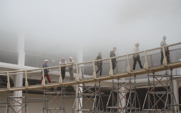 People walking via a ramp into a cloud