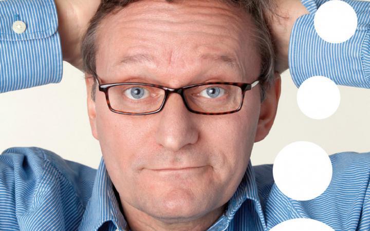 Ein Mann mit Brille schaut in die Kamera. Seine Arme sind hinter dem Kopf verschränkt.