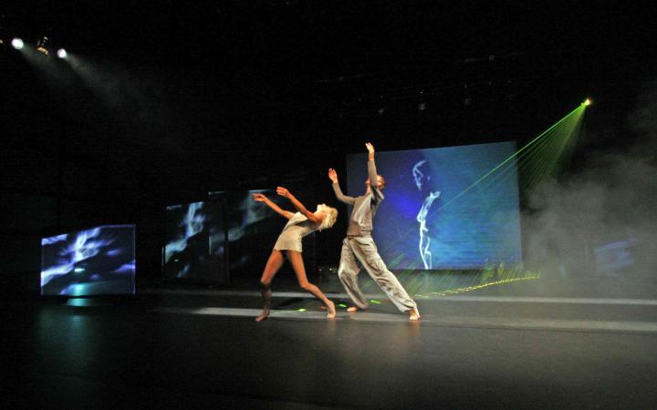Zwei Personen auf einer Bühne mit Lichteffekten