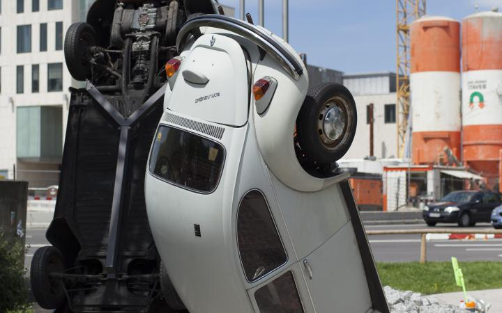 A white VW beetle standing on his head