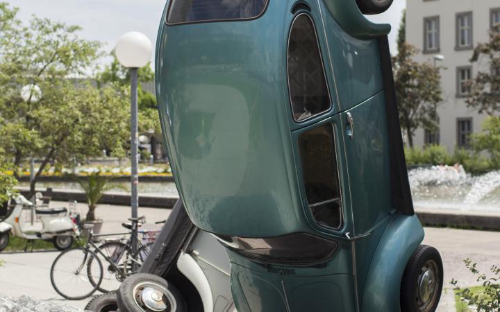 Ein grüner VW-Käfer der auf dem Kopf steht