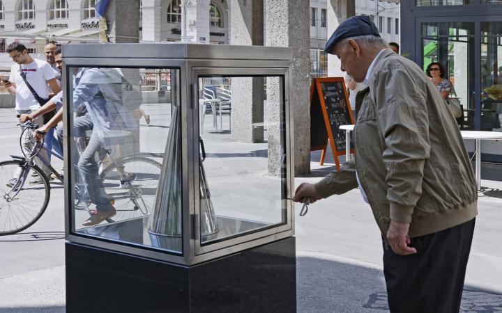 A man takes a silver megaphone from a glass cabinet