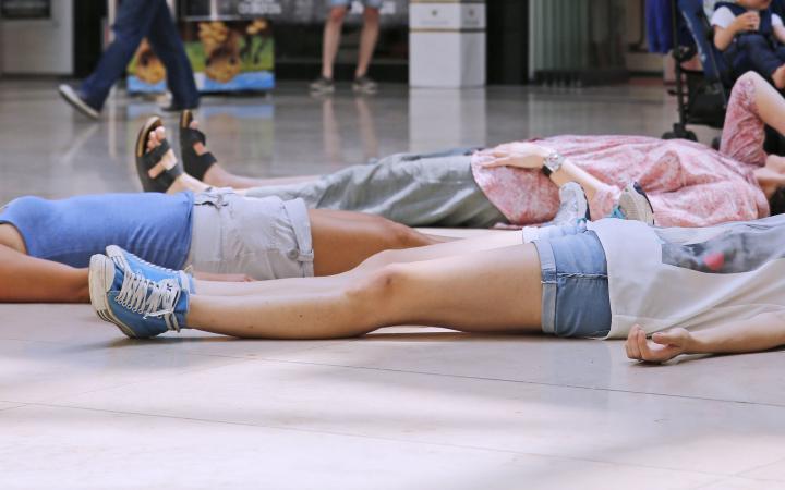 Drei Personen liegen mit dem Rücken auf dem Boden