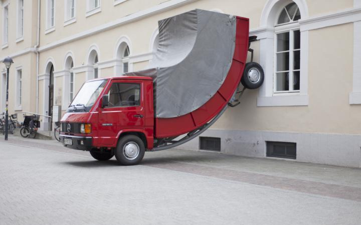 A red truck whose rear wheels stand at the wall