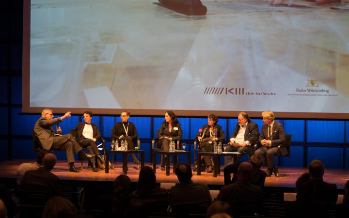 Seven people sit in a semicircle on a stage and discuss with eachother.