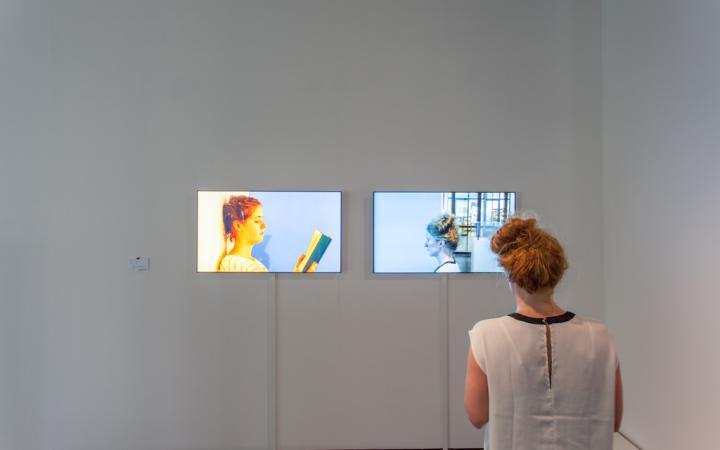 Eine Frau steht vor zwei Monitoren