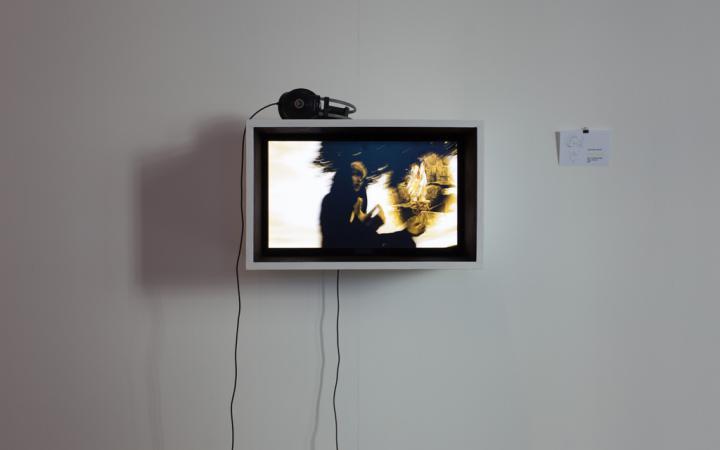 An der Wand hängt ein Monitor, auf dem ein Film läuft