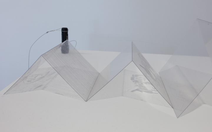 Ein zu Pyramiden gefaltetes Stück Plastik, auf dem ein Gesicht zu sehen ist.