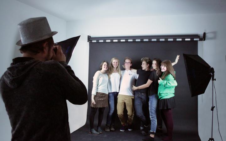 Eine Gruppe junger Menschen vor einer schwarzen Leinwand, die in die Kamera lächeln