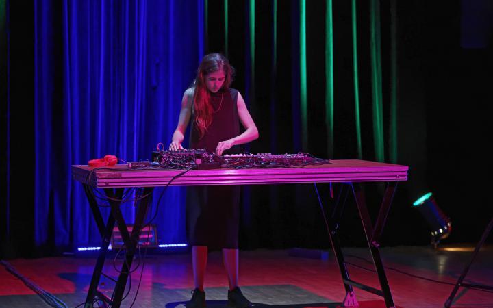 Ein Frau steht an einem Tisch und dreht an Knöpfen