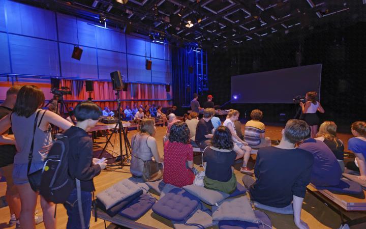 Menschen sitzen auf dem Boden um eine Bühne