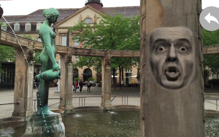 Blick auf den Stephanienbrunnen am Stephansplatz: auf der Säule ist die Projektion eines sprechenden, männlichen Gesichts zu sehen.