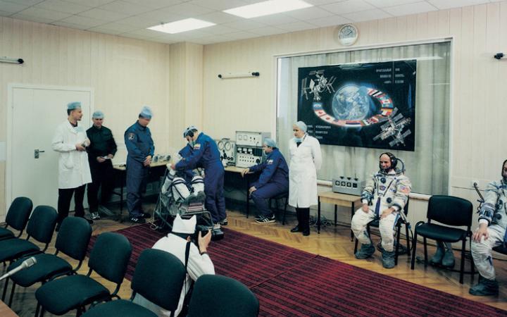 Ein Konferenzraum. Mehrere Astronauten und Mediziner.