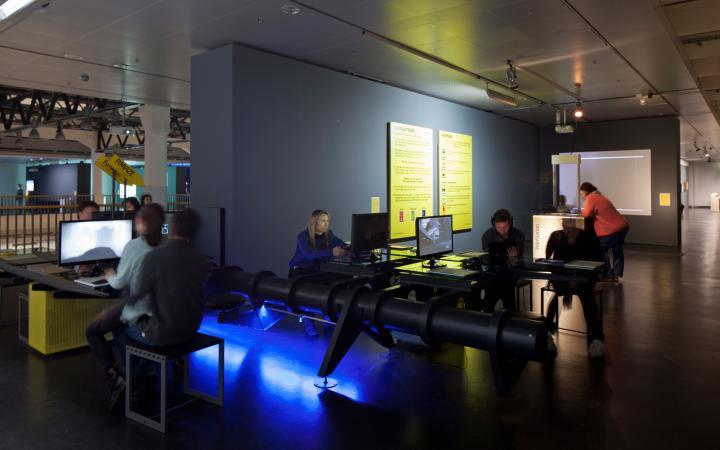 Ein Raum. Mehrere Menschen, die an verschiedenen Spielekonsolen sitzen.