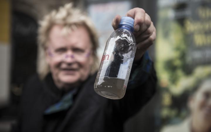 Ein Mann hält eine Wasserflasche in die Kamera