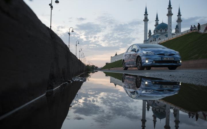A blue car next to a water puddle