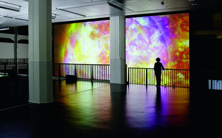 A huge screen of datamatrix, and very small in front of it a woman standing at a railing