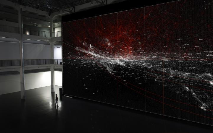 Eine Frau vor einer riesigen Wand, auf der rote und weiße Sprenkel zu sehen sind