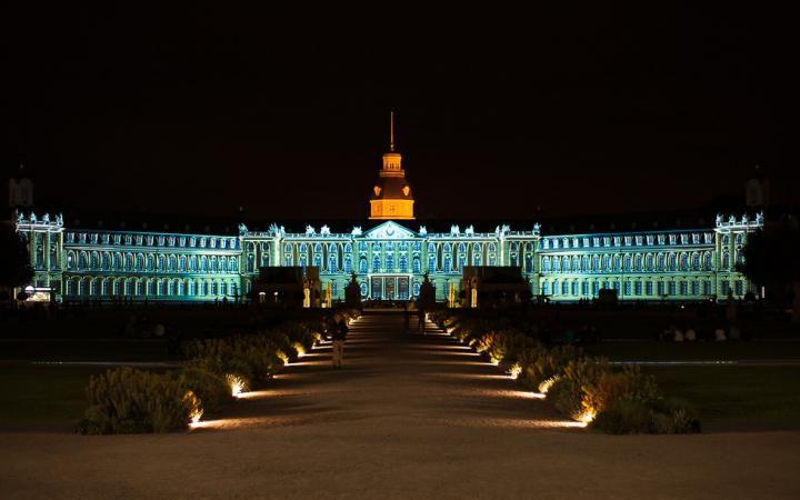 Die Karlsruher Schlossfassade in grün-blauem Licht
