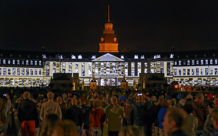People standing in fron of the Karlsruhe palace, on which figures are projected
