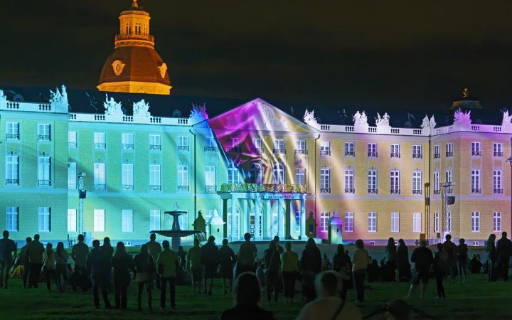 Das Karlsruher Schloss ist in türkis und rosa Licht getaucht