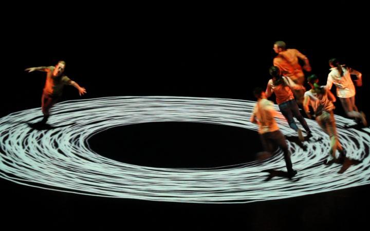 Menschen rennen im Kreis, der auf dem Boden angezeichnet ist.