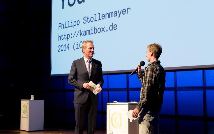 Zwei Männer unterhalten sich auf der Bühne